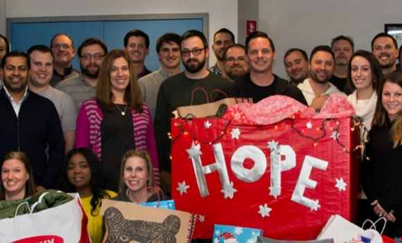 Applause group photo with presents for the United Way's Holiday Hope for the Holidays