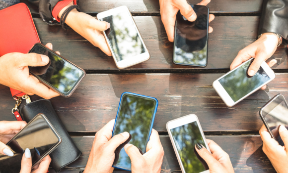 Eight hands holding mobile phones in a circle at a picnic table.