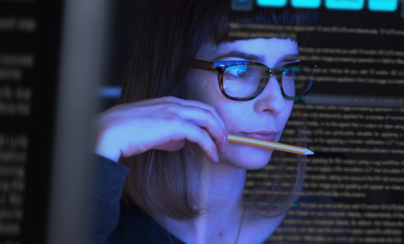Woman analyzing raw data on screen in front of her.