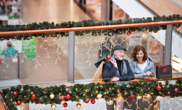 A couple smiling at a shopping mall during the holidays.