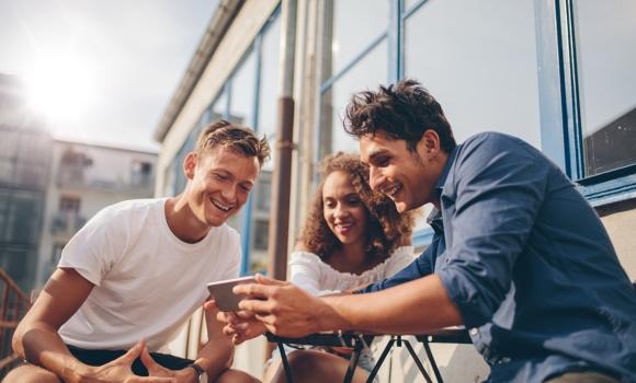 Grupo de amigos haciendo uso de una app de comercio electrónico en su dispositivo móvil, pruebas crowdtesting para un customer journey con éxito.