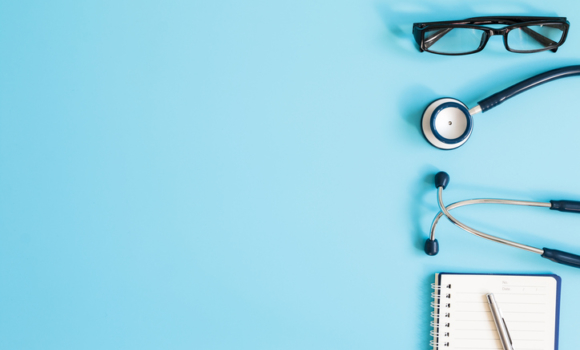 A stethoscope, pen, and notebook on a blue background.