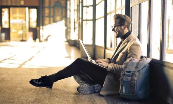 Person, die auf dem Boden, Laptop betrachtend sitzt