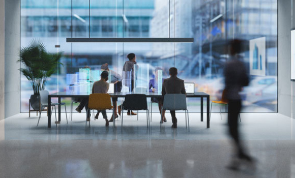 People move about in a futuristic office room.