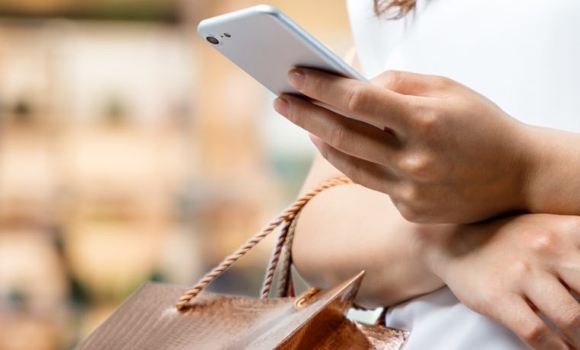 Woman in white shirts holds phone in left hand and shopping bag in right hand.