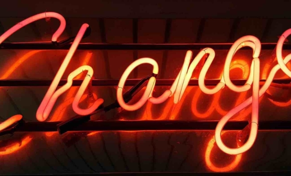 "A neon sign with the word ""Change"" lit up in red."
