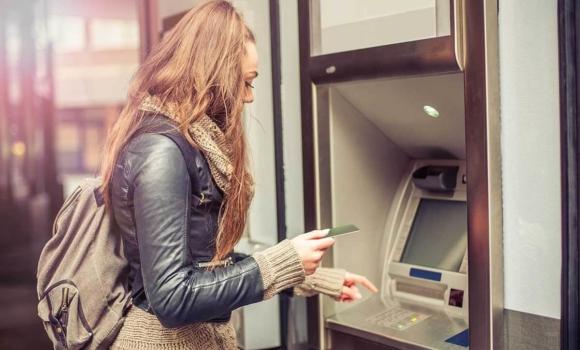 Person, die Geld am Geldautomaten abhebt