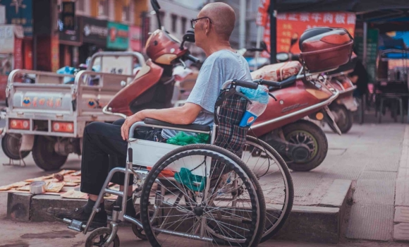 Man sitting on wheelchair near street with a motorbike in the background.