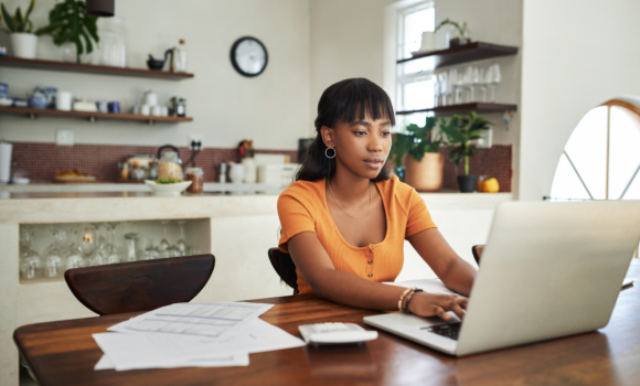 A young woman works on her laptop at home.