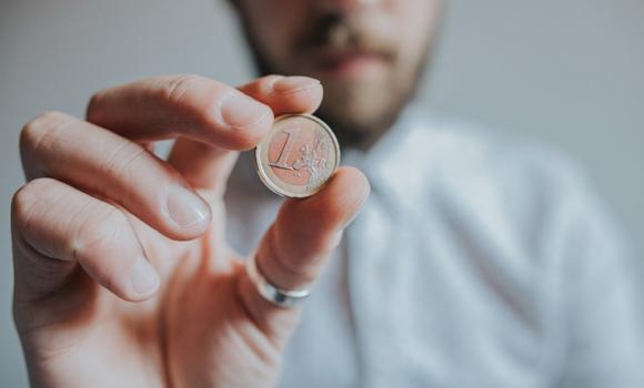 personne tenant une pièce d'un euro