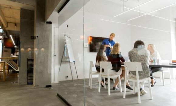 Les membres d'une communauté de pratique de test se réunissent et travaillent ensemble sur différents sujets dans une salle de réunion.