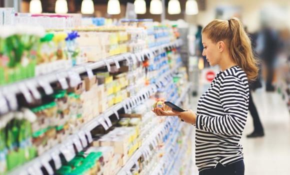 consommatrice frnaçaise utilise un appli foodtech pour scanner des produits dans un supermarché et mieux manger au quotidien