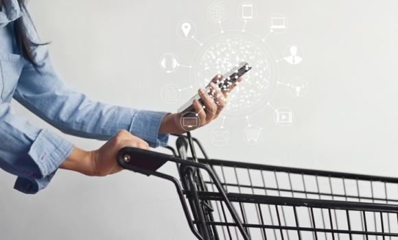 Usuario de comercio minorista haciendo la compra mientras disfruta de una experiencia digital personalizada de la marca con su dispositivo móvil.