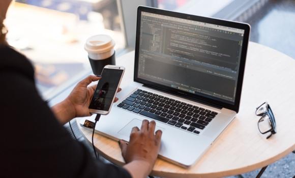 Person schaut auf Smartphone und Macbook Pro und programmiert eine App