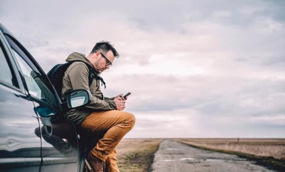 Homme assis sur une voiture en regardant son téléphone