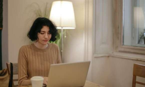 QA manager assise a son bureau devant son ordinateur, travaille de chez elle.