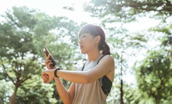 Une femme utilise une application sport tech avec sa montre connectée lors de son entrainement de sport.