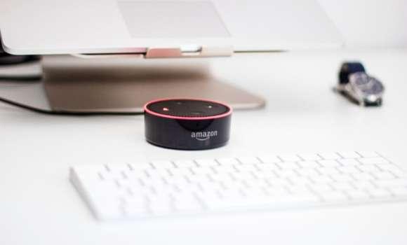 Amazon Echo Dot steht auf einem Schreibtisch vor einem Laptop mit Tastatur und wird zur Sprachsuche mit Hilfe von Alexa Skills genutzt.