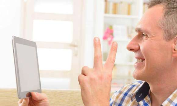Person with hearing aid using tablet