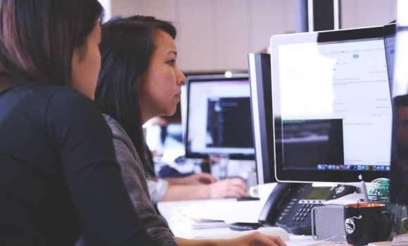 Zwei Frauen, die Bildschirm betrachten, automatisierte Testzyklen zu betrachten.