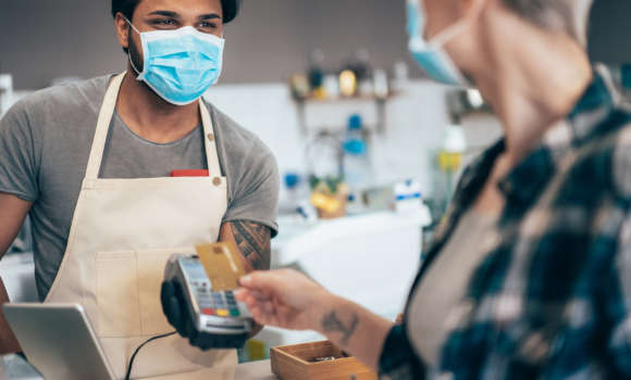 Young barista and modern woman paying contactless at cafe wearing face protective mask to prevent Coronavirus and other diseases.