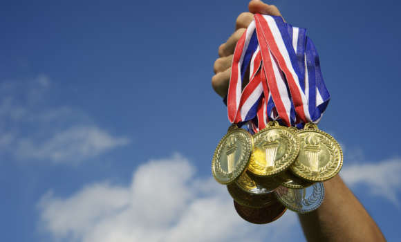 A hand holds up several gold medals.
