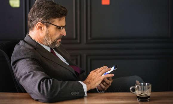 Mann in einem Anzug, der sein Online-Bankkonto auf seinem Smartphone überprüft.