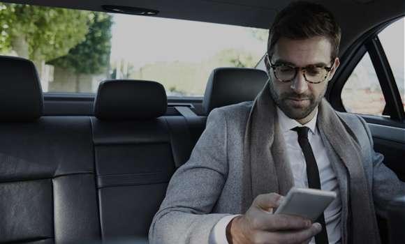 Man behind a car looking at his phone