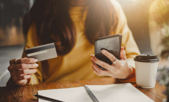 Young woman using smart phone and credit card for shopping online