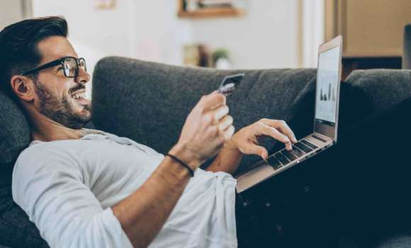 Man lying on couch with laptop on his legs finalizing purchase with credit card in right hand.
