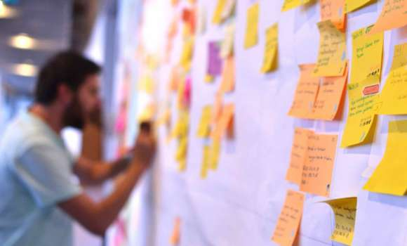 Man placing Post-It notes on Scrum board.