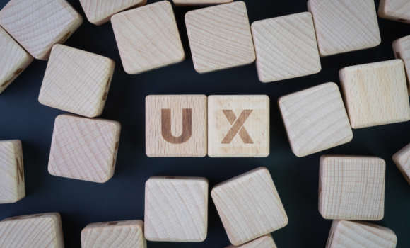 Scrabble tiles spelling out 'UX'.