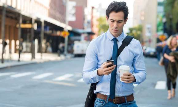 Man on busy street looking at his phone
