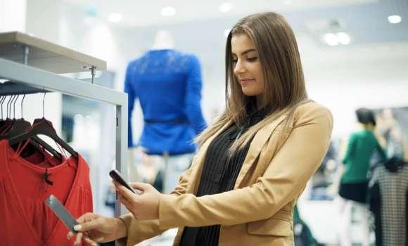 Person, die Foto des Tags auf Hemd mit Telefon in einem Einzelhandelsgeschäft macht