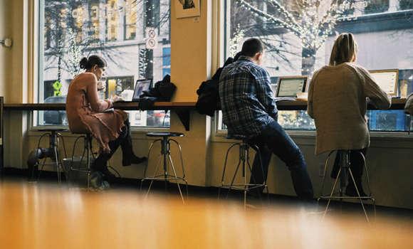 Menschen sitzen im Café, betrachten Laptops.
