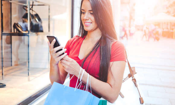 Woman looking on her phone after shopping