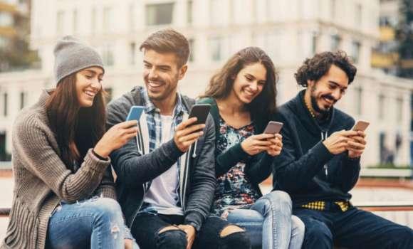 People smiling looking at their phones