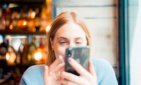 Mobile Nutzerin betrachtet ihr Telefon im Café.