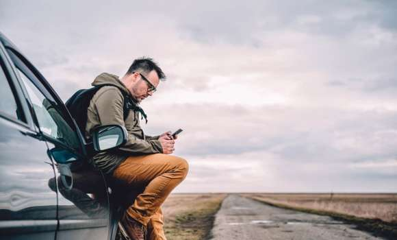 Man sitting on car looking at his phone