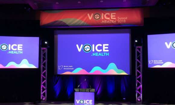 A photo of the stage at the Voice.Health Summit in Boston.