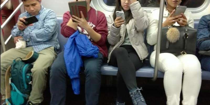 Kids on train looking at their devices