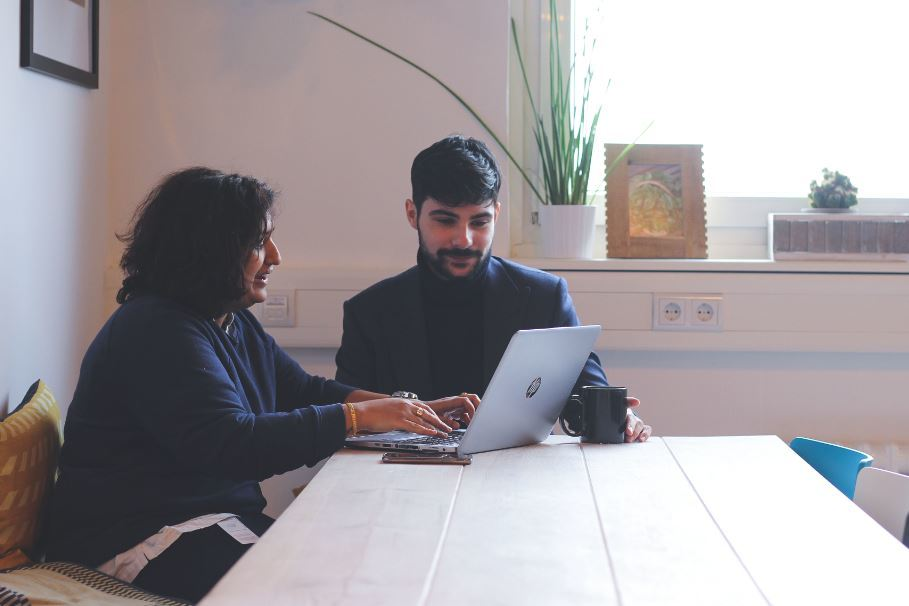 two people sitting at a table on a laptop