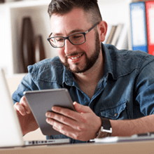 man with glasses holding iPad