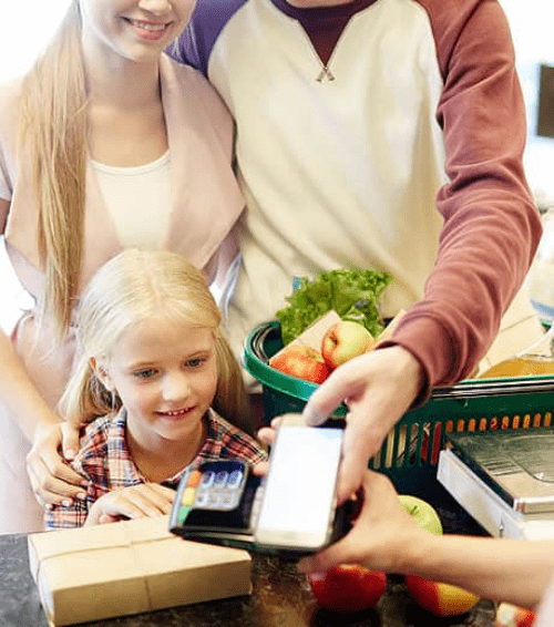 Family buying groceries with phone payment