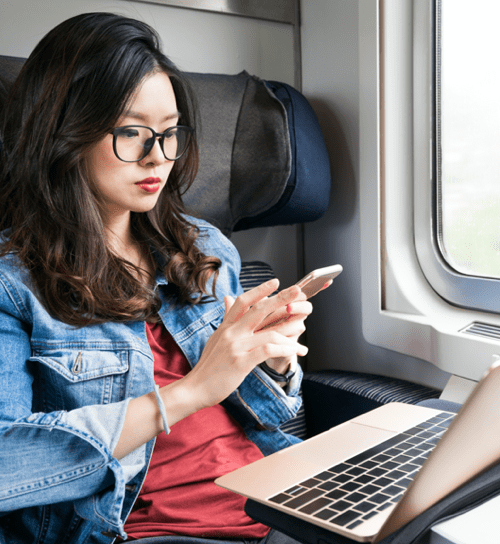 Woman in a train on her phone and laptop