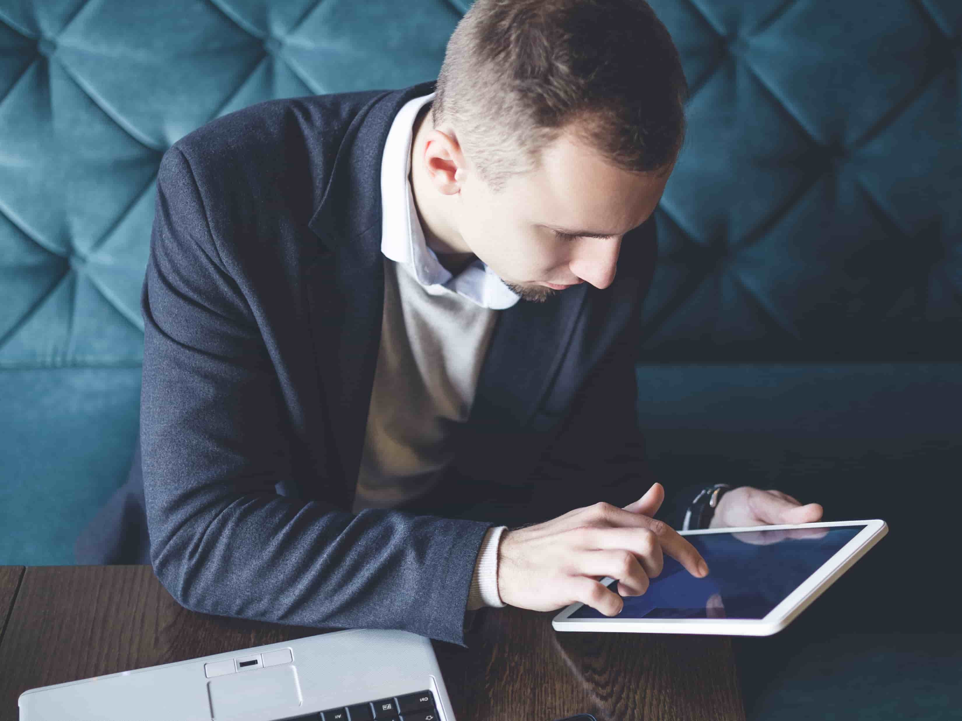 Homme en costume regarde tablette